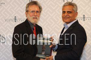 Ken Eberts (left) receives Lincoln Award fro Elegance from Kumar Galhotra