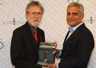 Ken Eberts (left) receives Lincoln Award for Elegance from Kumar Galhotra